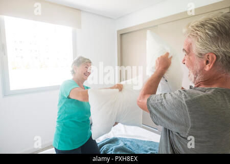 Happy caucasian aged senior adult couple enjoy the early morning making a pillows war together playing and laughing a lot. love and married forever li - Stock Photo