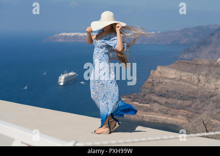 young woman in a white and blue dress enjoys a walk around Santorini