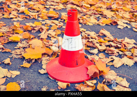 Traffic cone and dry fallen autumn leaves on the concrete asphalt - Stock Photo