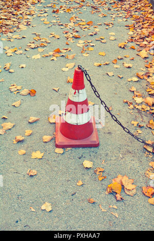 Traffic cone with rust chain and dry fallen autumn leaves on the concrete asphalt - Stock Photo