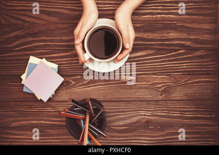 women's hands holding coffee Cup stickers and pencils on wooden background with copy space on top. - Stock Photo