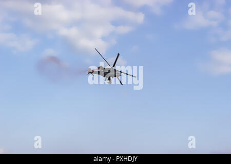 Combat helicopter on blue sky with white clouds. View from the bottom. - Stock Photo