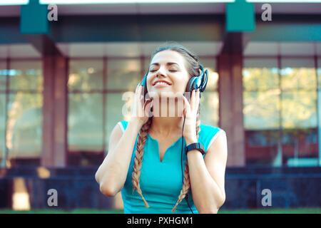 Athletic woman enjoying music in headphones  - Stock Photo