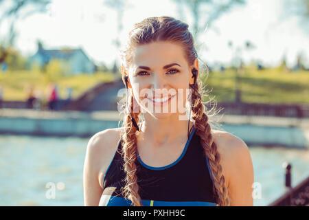 Portrait of beautiful sportive woman in sunlight - Stock Photo