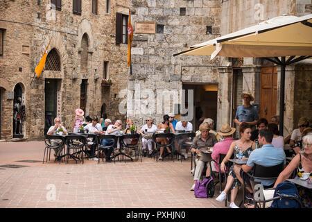 Tourists in Piazza Della Cisterna (Cistern Square)  in hilltop town of San Gimignano, Tuscany, Italy - Stock Photo