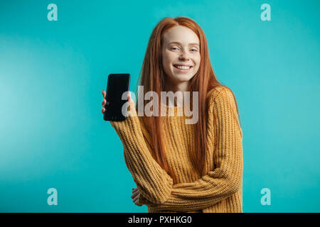 Portrait of a redhaired woman holding smartphone over blue background - Stock Photo