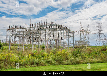 Horizontal shot of an Electric Power Grid Station under cloudy skies. - Stock Photo