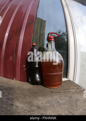 Plastic Wine Bottles Stand in the courtyard on the windowsill - Stock Photo
