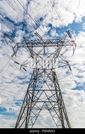 Vertical shot of High Voltage Power Lines and Tower under cloudy skies.  Looking upward. - Stock Photo