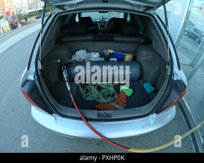 Filling the car with methane gas bottle in the trunk - Stock Photo