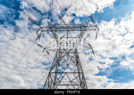 Horizontal shot of a High Voltage Tower and Power Lines under cloudy skies. Stock Photo