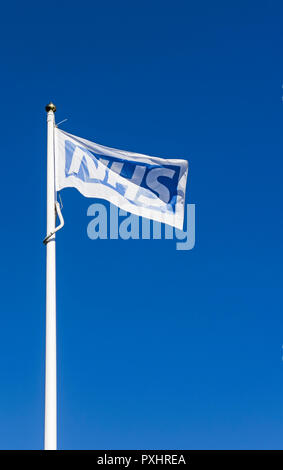 An NHS flag flying on a flagpole against a background of blue sky - Stock Photo