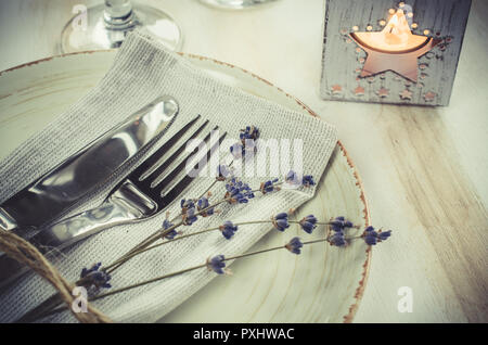 Festive table setting at vintage or provence style with candles and lavender. Concept Birthday, Valentine's, Mother's or Father's Day. Closeup. - Stock Photo