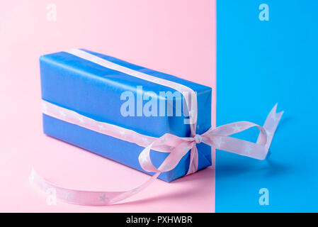 Minimal style image with a birthday gift wrapped in blue paper and pink ribbon, on a paper background in blue and pink colors. - Stock Photo
