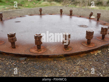 Rusty steel plate and rusty steel bolts and nuts on concrete base in coastal location nr Pwllheli north wales uk - Stock Photo