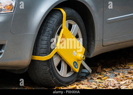 Yellow wheel clamp on parked car in Plovdiv, Bulgaria - Stock Photo