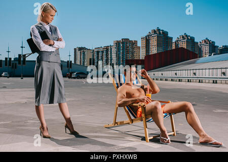 handsome young man relaxing on sun lounger while his lady boss in suit standing next to him with crossed arms on parking - Stock Photo