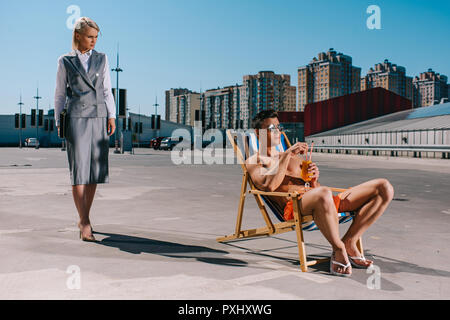 handsome young man relaxing on sun lounger while his lady boss in suit standing next to him on parking - Stock Photo