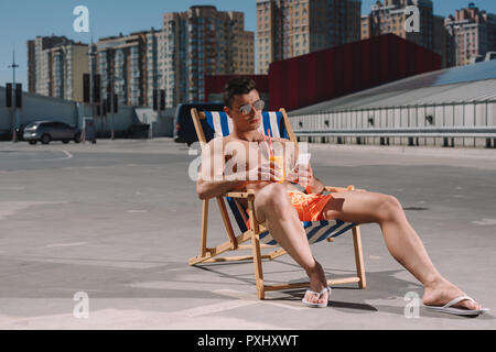 young shirtless man relaxing on sun lounger with cocktail and using smartphone on parking - Stock Photo