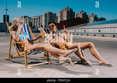 young couple with glasses of cocktails while sitting on sun loungers on parking - Stock Photo