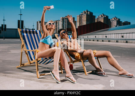 young couple relaxing on sun loungers with cocktails and taking selfie on parking - Stock Photo