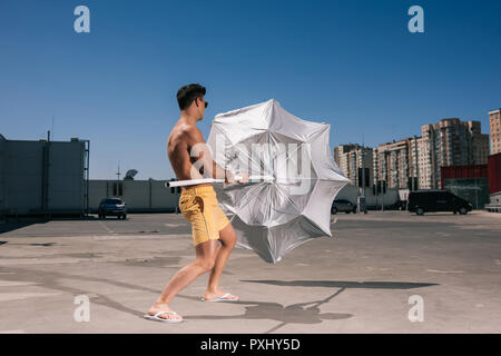 handsome young shirtless man with beach umbrella on parking - Stock Photo