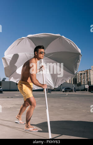 handsome young man putting beach umbrella in asphalt on parking - Stock Photo
