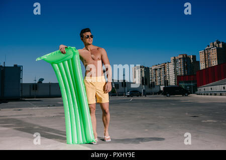 happy young shirtless man with inflatable bed on parking - Stock Photo