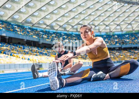 young male and female joggers sitting on running track and stretching at sports stadium - Stock Photo