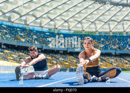 young sportive male and female joggers sitting on running track and stretching at sports stadium - Stock Photo