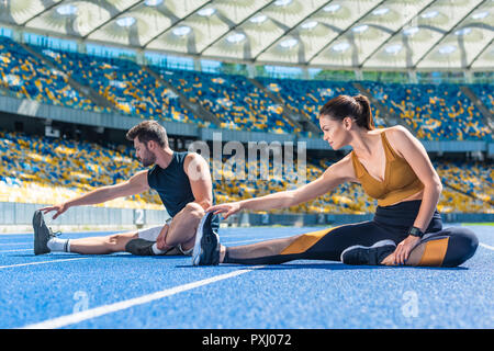 young athletic male and female joggers sitting on running track and stretching at sports stadium - Stock Photo