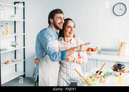 boyfriend pointing on something to girlfriend during cooking in kitchen - Stock Photo