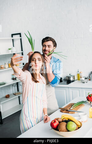 couple taking selfie while having fun during cooking in kitchen - Stock Photo