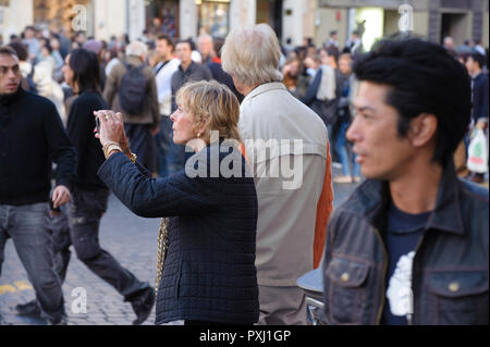 Senior woman in a crowd taking a picture with her mobile phone. Rome, Italy. - Stock Photo