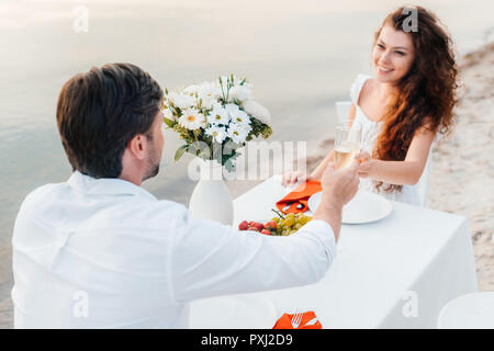 man and woman toasting with champagne glasses during romantic date on beach - Stock Photo