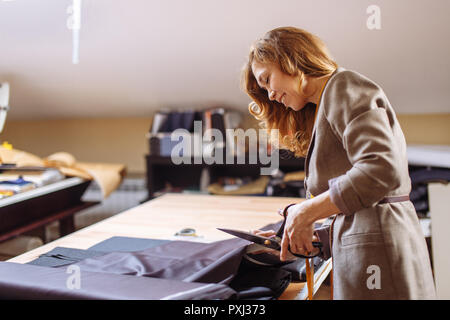 Female fashion designer working on suiting fabric with dressmaking accessories on table - Stock Photo