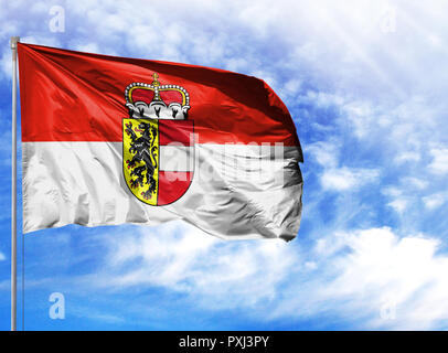 National flag of Salzburg on a flagpole in front of blue sky. - Stock Photo