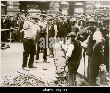 Labourers making a trail in the pavement, for some kind of maintenance, watched by a crowd of people.     Date: 1927 - Stock Photo