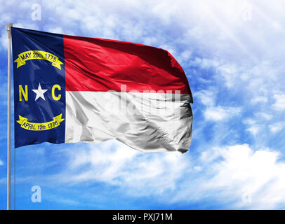 flag State of North Carolina on a flagpole in front of blue sky. - Stock Photo