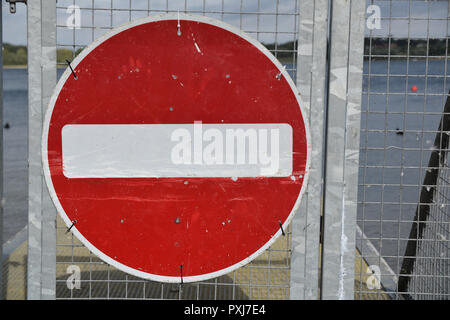 Circular No Entry sign with white bar on red background on a metal gate with lake in the background - Stock Photo