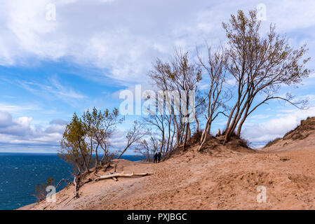Two people walking under trees growing on the top of a sand dune at Sleeping Bear Dunes National Lakeshore, Empire, Michigan, USA. - Stock Photo