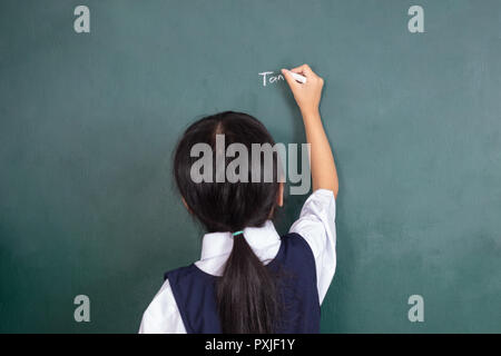 Asian Chinese little girl writing on blackboard in the classroom - Stock Photo