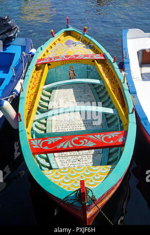 Colourfully painted fishing boat with religious texts in the harbour of the fishing village Aci Trezza - Stock Photo
