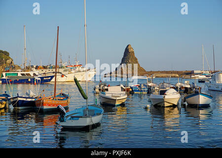 Evening atmosphere in the harbour of the fishing village Aci Trezza, behind it the cyclopean island Faraglione grande - Stock Photo