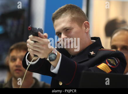 Moscow, Russia. 23rd Oct, 2018. MOSCOW, RUSSIA - OCTOBER 23, 2018: A policeman aims a pistol at the Interpolitex 2018 International Exhibition of Means of State Security Provision held at Moscow's VDNKh Exhibition Centre. Stanislav Krasilnikov/TASS Credit: ITAR-TASS News Agency/Alamy Live News - Stock Photo