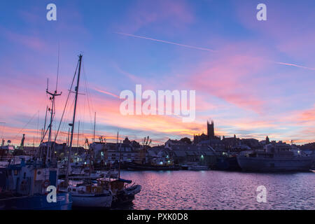 Penzance harbour, Cornwall, UK. 23rd October 2018. UK Weather. It was a colourful sunset over Penzance this evening. On the opposite horizon the nearly full moon rising was obscured by clouds. Credit: Simon Maycock/Alamy Live News - Stock Photo