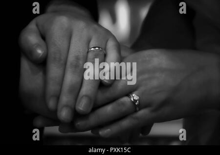 Bride and groom showing off rings - Stock Photo