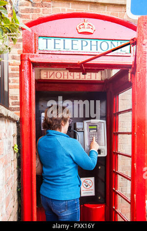 Woman chatting talking using a telephone in an traditional red English telephone box kiosk design  no 6  / K6 designed in 1935 by Sir Gilbert Scott - Stock Photo