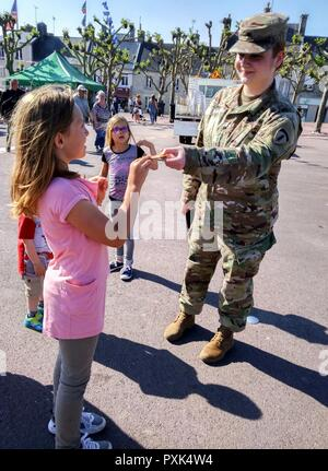 Spc. Kelsey Little, a photojournalist from U.S. Army Europe Public Affairs, gives her American flag patch as a souvenir to a girl after the Airborne Troops Monument Ceremony in Sainte-Mere-Eglise, France. The ceremony commemorates the 73rd anniversary of D-Day, the largest multi-national amphibious landing and operational military airdrop in history, and highlights the U.S.' steadfast commitment to European allies and partners. Overall, approximately 400 U.S. service members from units in Europe and the U.S. are participating in ceremonial D-Day events from May 31 to June 7, 2017. - Stock Photo