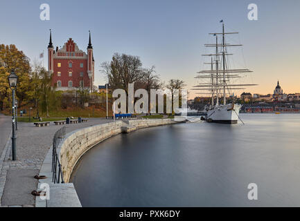 Western shore of Skeppsholmen in Stockholm, Sweden, with a sail boat on its tip - Stock Photo